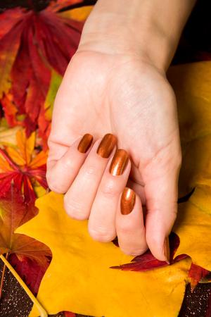 高角クローズ アップ女性の指に青銅色のマニキュアを適用するコピー スペースと白い面で近くに爪ブラシを用いたボトル 写真素材