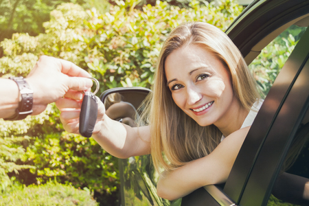 handover: young smiling woman sitting in car taking key handover rent  purchase