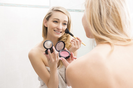 enhance: Smiling attractive young blond woman applying blusher to her cheek from a handheld compact using a large cosmetics brush, focus to her reflection in the mirror in a beauty concept Stock Photo
