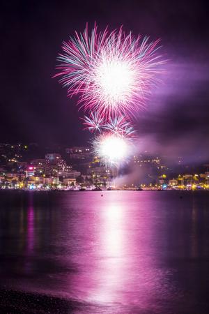 mimose: Summer Festival con brillante fuochi d'artificio colorati che esplodono in città Waterfront, Bormes-les-Mimosas, Provenza-Alpi-Costa Azzurra, Francia