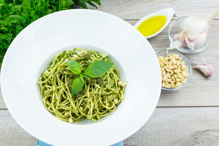 olive green: Homemade basil pasta with green pesto in wide brim bowl on wooden table with bowls of cheese, garlic, olive oil and cilantro Stock Photo