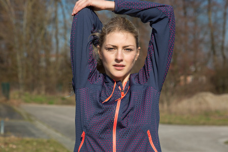 limbering: Young woman stretching to warm up her muscles as she stands outdoors alongside a rural road with woodland ready to go for her morning jog, upper body smiling at camera Stock Photo