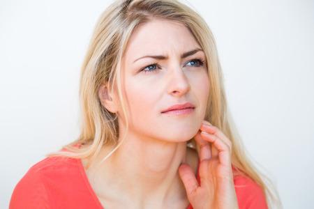 Taille-up portret van jonge blonde vrouw met lang haar, op zoek naar de kant in diepe gedachten met hand in haar en Verward Gezichtsuitdrukking, in de studio met witte achtergrond