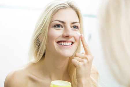fresh women: Pretty young woman wrapped in a white towel standing smiling in front of the mirror applying a cream or moisturizer to her face in a skincare and beauty concept