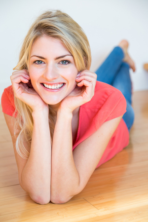 Waist Up Portrait of Confident Young Blond Woman with Long Hair Lying on Wooden Floor on Stomach with Hand on Chin, Smiling and Looking Happy at Home