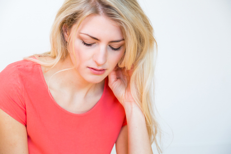 glum: Waist Up Portrait of Young Blond Woman with Long Hair and Hand Resting on Chin, Looking Down with Depressed or Sad Expression