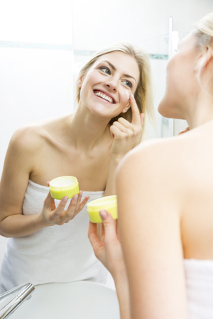 unblemished: Pretty young woman wrapped in a white towel standing smiling in front of the mirror applying a cream or moisturizer to her face in a skincare and beauty concept