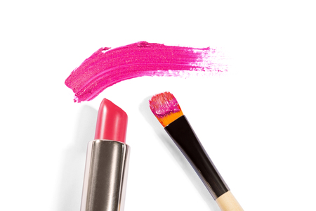 smudge: High Angle Still Life of Tube of Pink Lipstick with Applicator Brush and Smudge of Pink Make Up Across White Background with Copy Space