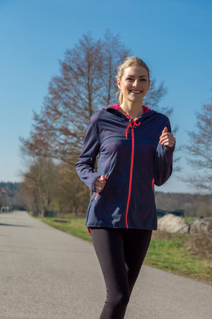 Active young woman out jogging on a rural road as she gets her daily exercise in a healthy lifestyle concept Stock Photo