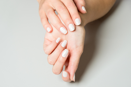 Two hands of woman with manicured and painted fingernails for spa treatment concept Zdjęcie Seryjne