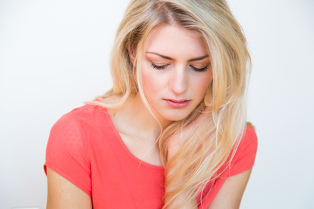 Waist Up Portrait of Young Blond Woman with Long Hair and Hand Resting on Chin, Looking Down with Depressed or Sad Expression
