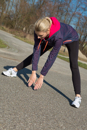 muscle toning: Young woman warming up doing stretching exercises on a rural road before she starts her daily jog in a health and fitness concept