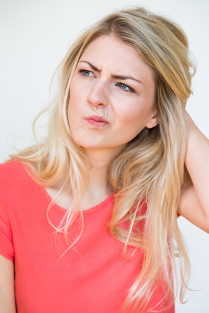 quizzical: Waist Up Portrait of Young Blond Woman with Long Hair, Looking to the Side in Deep Thought with Hand in Hair and Perplexed Facial Expression, in Studio with White Background