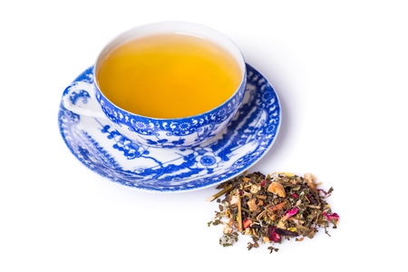 the next life: High Angle Still Life of Herbal Tea in Decorative Blue and White Cup with Saucer Next to Pile of Dried Gourmet Herbal Tea Mixed with Flower Petals on White Background with Copy Space