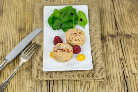baby spinach: High Angle View of Goose Liver Pate Garnished with Baby Spinach Salad and Raspberries Served on Rectangular Plate, Burlap Placemat and Rustic Wooden Table with Knife and Fork