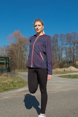 limbering: Young woman warming up doing stretching exercises on a rural road before she starts her daily jog in a health and fitness concept