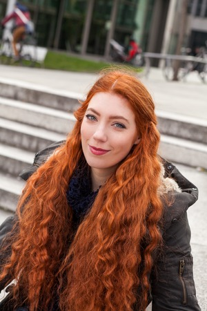 pleased: Pleased young woman with long red hair stands outside by a row of concrete stairs with a smile on her face