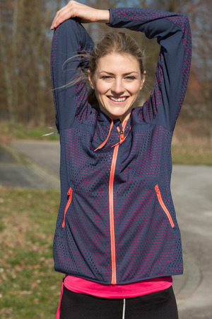 upper body: Young woman stretching to warm up her muscles as she stands outdoors alongside a rural road with woodland ready to go for her morning jog, upper body smiling at camera Stock Photo