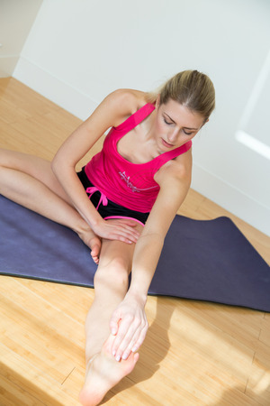 cardiovascular exercising: Attractive fit blond woman smiles while stretching one leg and holding toes seated on yoga mat near white wall