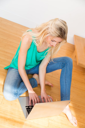 sleeveless top: Young blond woman wearing blue jeans and green sleeveless top sitting on a wooden floor and typing on her computer