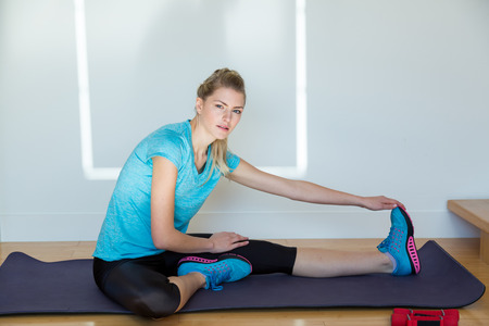 cardiovascular exercising: Athletic woman with braided hair wearing blue top and gym shoes stretches on yoga mat near wooden stairs and a white wall Stock Photo