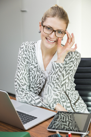 hardworking: Attractive hardworking woman adjusting glasses while working at desk on laptop and tablet computer in small office Stock Photo