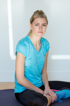 knee bend: Solitary young athletic blond woman wearing blue top and spandex pants sits by white wall on a dark blue mat Stock Photo