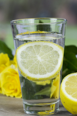 tangy: Glass of fresh cold mineral water with a slice of fresh lemon for a tangy taste on a table with yellow roses in a healthy diet and lifestyle concept Stock Photo