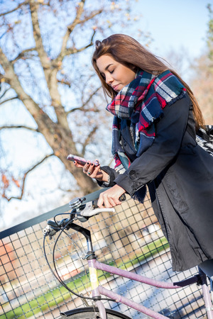 checkered scarf: Single cute female in coat and plaid scarf parked near fence looking down at her cell phone with large bare tree in background