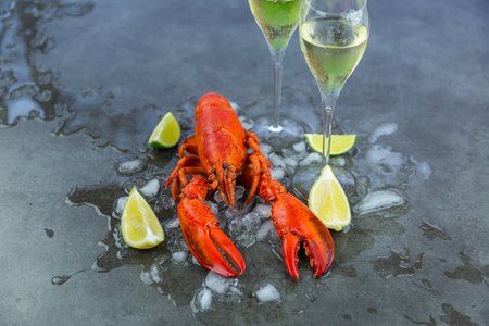 Fresh Lobster Chilling on Ice with Wedges of Lime and Two Glasses of Celebratory Sparkling Wine or Champagne - Still Life of Celebratory Lobster Dinner with Wine Stock Photo