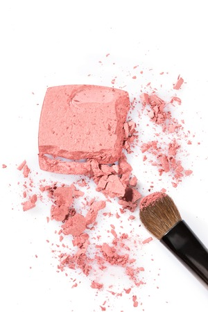 tipped: Close up High angle view of broken pink cosmetic powder with thick tipped brush against a white background
