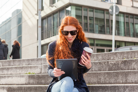 concrete steps: Trendy young red head wearing black boots and blue jeans seated on concrete steps smiles at her tablet on a sunny day