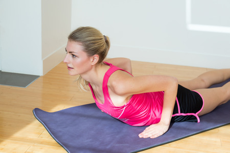 sleeveless top: Slender blond woman with ponytail in pink sleeveless top and black shorts stretches her torso while on her stomach