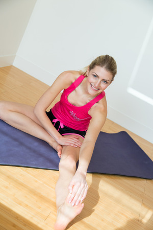 touching toes: Attractive fit blond woman smiles while stretching one leg and holding toes seated on yoga mat near white wall
