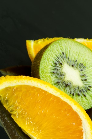 obscured: Extreme close up on black seeds in juicy green kiwi fruit slice with orange pieces obscured in background Stock Photo
