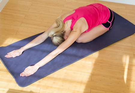 cardiovascular exercising: blond young woman wearing pink top and black shorts stretches her arms while face down on a yoga mat and wooden floor Stock Photo