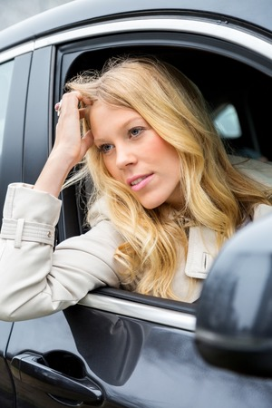 glum: Bored attractive young woman sitting waiting in a car staring out through the open window with a glum expression