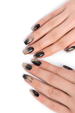 manicured hands: Close up of stylish manicured hands painted black and glittery gold against a white background