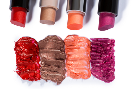 smudge: High Angle Still Life of Four Tubes of Various Lipsticks in Assortment of Shades and Lined Up on White Background with Smudge Samples of Color