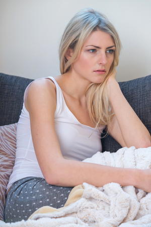 glum: Single serious blond woman in sleeveless shirt partially covered in blanket on blue sofa looking at something