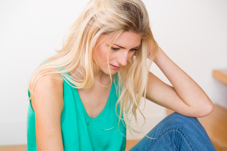 sleeveless top: A smiling young blond woman wearing blue jeans and green sleeveless top sits by white wall and wooden stairs