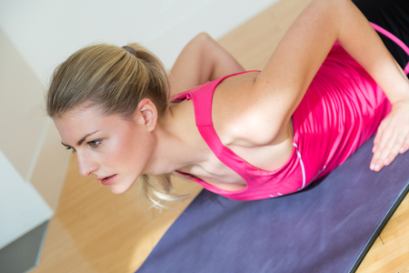 Slender blond woman with ponytail in pink sleeveless top and black shorts stretches her torso while on her stomach