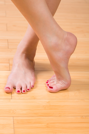 u�as pintadas: De arriba hacia abajo Cierre de vista sobre u�as de los pies y las u�as perfectamente pintadas sobre suelo de madera dura
