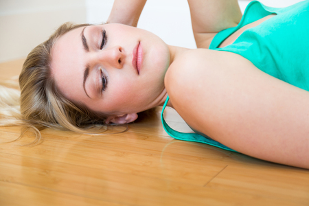 dispirited: High angle view on cute serious blond young adult woman in green undershirt holding side of neck while laying down on hardwood floor Stock Photo