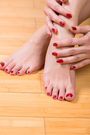 uñas pintadas: De arriba hacia abajo Cierre de vista sobre uñas de los pies y las uñas perfectamente pintadas sobre suelo de madera dura