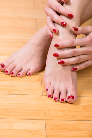 u�as pintadas: Top down close up view on neatly painted toenails and fingernails on hardwood floor