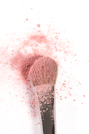 tipped: Overhead close up of one open jar of spilled pink blush powder with thick tipped brush on a white background