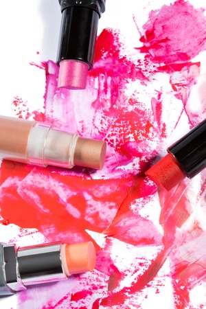 daubs: High Angle Close Up of Tube of Bright Pink Lipstick with Black Applicator Surrounded by Smudges of Vibrant Color on White Backgorund with Copy Space