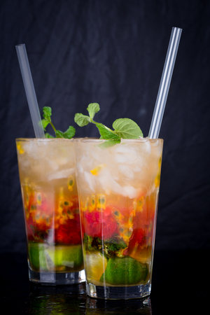 coctel de frutas: Colorful pair of cocktail drinks with fruit and straws on dark table with blue background