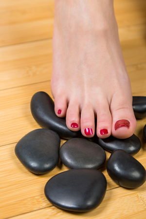 painted toenails: Pair of touching beautiful female feet with red toenails on smooth black relaxation stones over hardwood floor